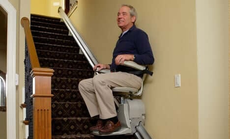 Older man riding on a Bruno Elan stairlift chair glide for stairs that are straight