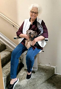 Senior woman with her dog in lap sitting on a stair lift in Denver, CO