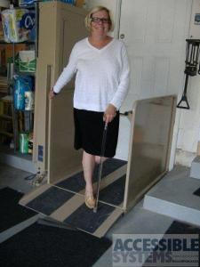 An older female adult rides her wheelchair lift smiling