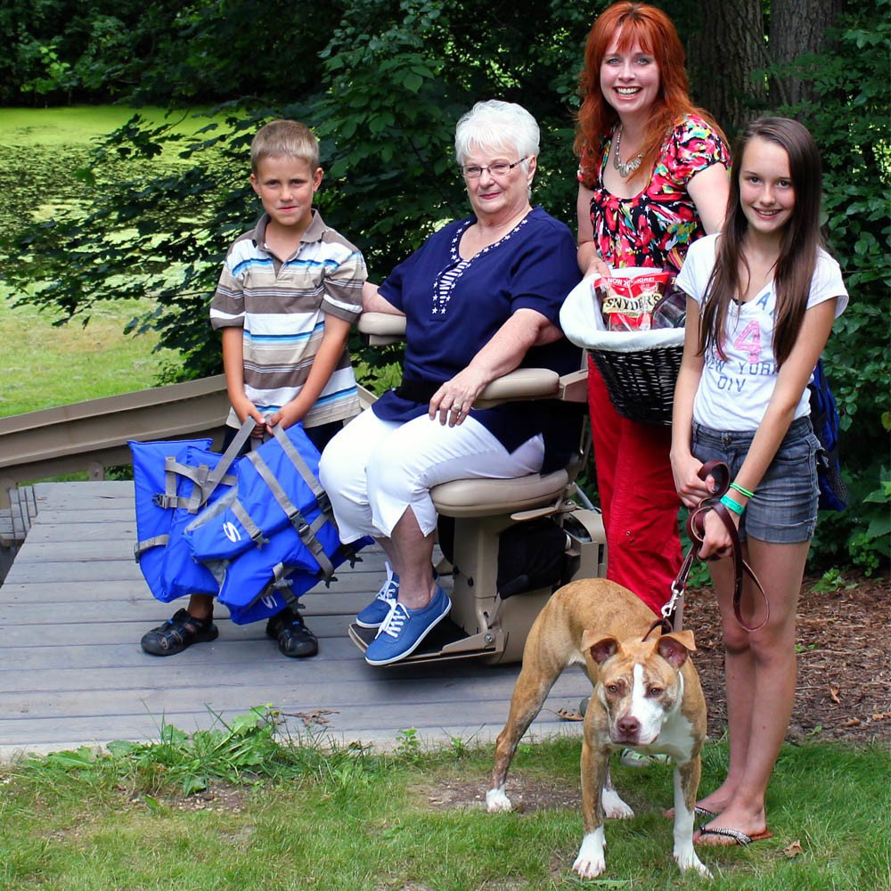 Home accessibility - A family smiling with grandma on her outdoor stair lift