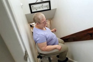 An older Caucasian woman riding down her Bruno straight stair lift