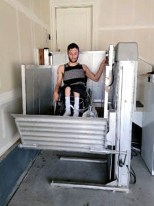 A disabled man in a wheelchair rides down an inclined platform lift installed in his Denver home